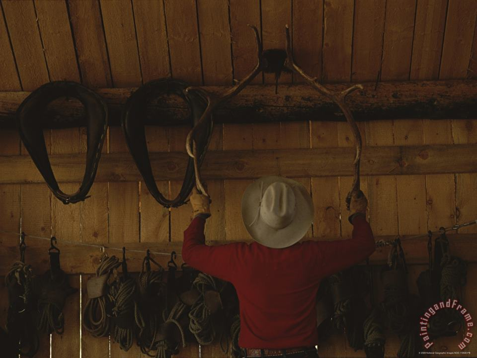 An Outfitter Hangs a Set of Elk Antlers on a Cabin Wall painting - Raymond Gehman An Outfitter Hangs a Set of Elk Antlers on a Cabin Wall Art Print